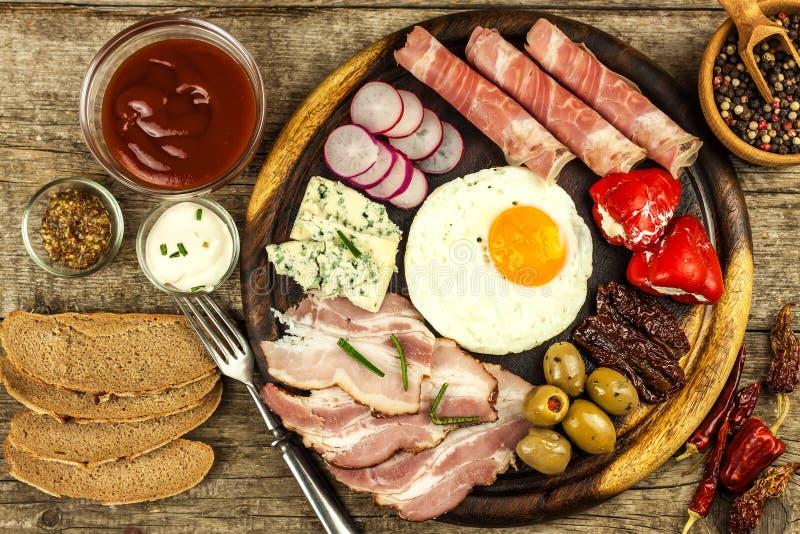 Huevo frito en un tablero de madera Un desayuno caluroso con el jamón y las verduras Huevos y jamón imagen de archivo