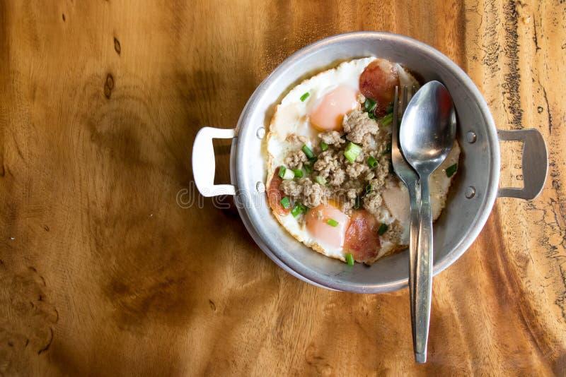Huevo frito hecho en casa, chuletas de cerdo y salchicha tailandesa en placa inoxidable en el fondo de madera del escritorio fotos de archivo