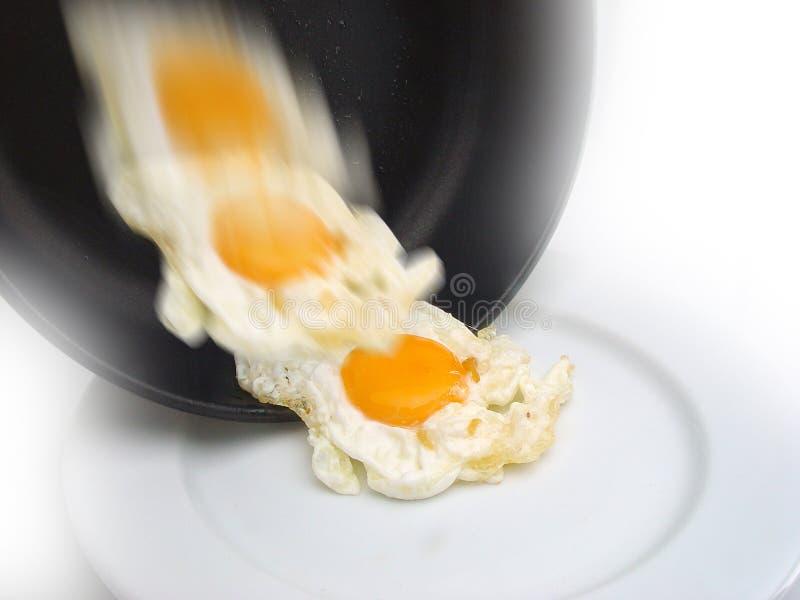huevo frito que resbala de una cacerola hacia la placa foto de archivo libre de regalías