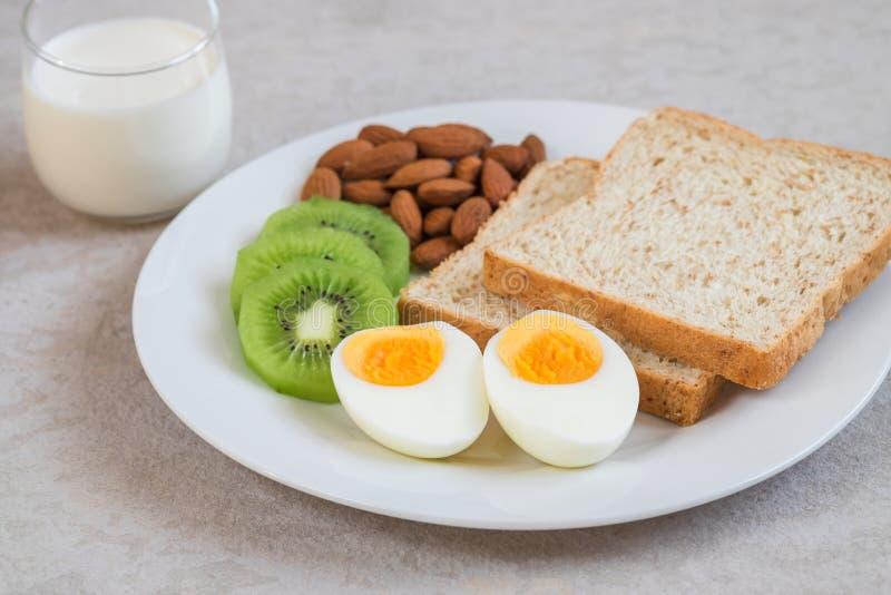 Huevo, pan del trigo integral, kiwi, almendras y leche hervidos, comida sana imagenes de archivo