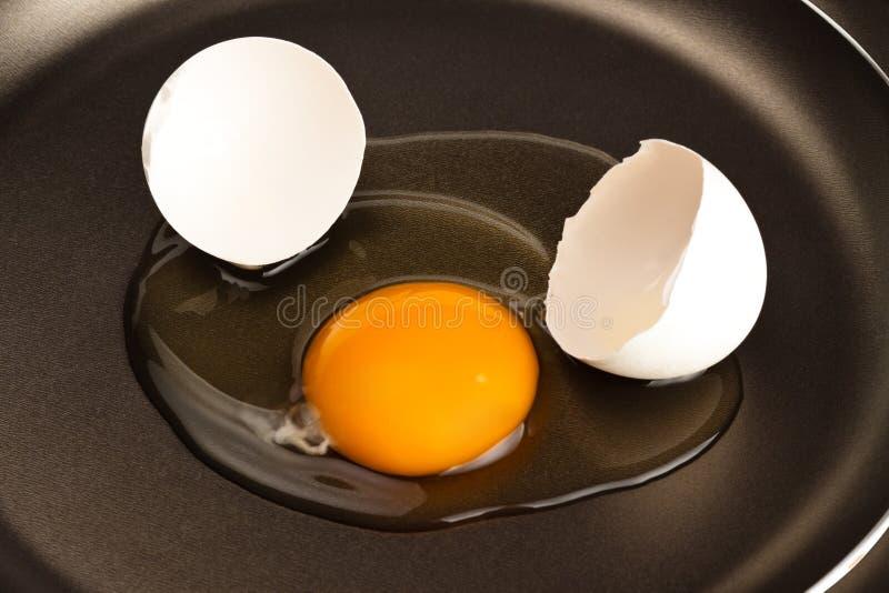 Huevo quebrado en la cacerola negra foto de archivo