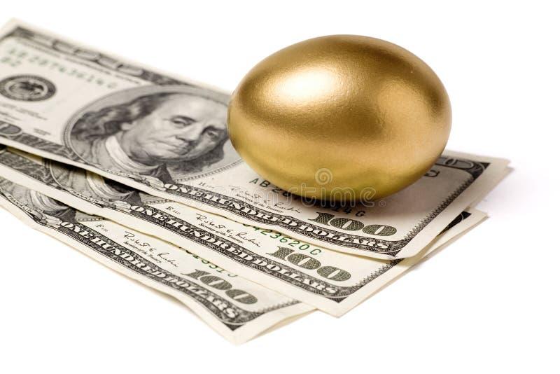 Huevo y dólares de oro fotografía de archivo