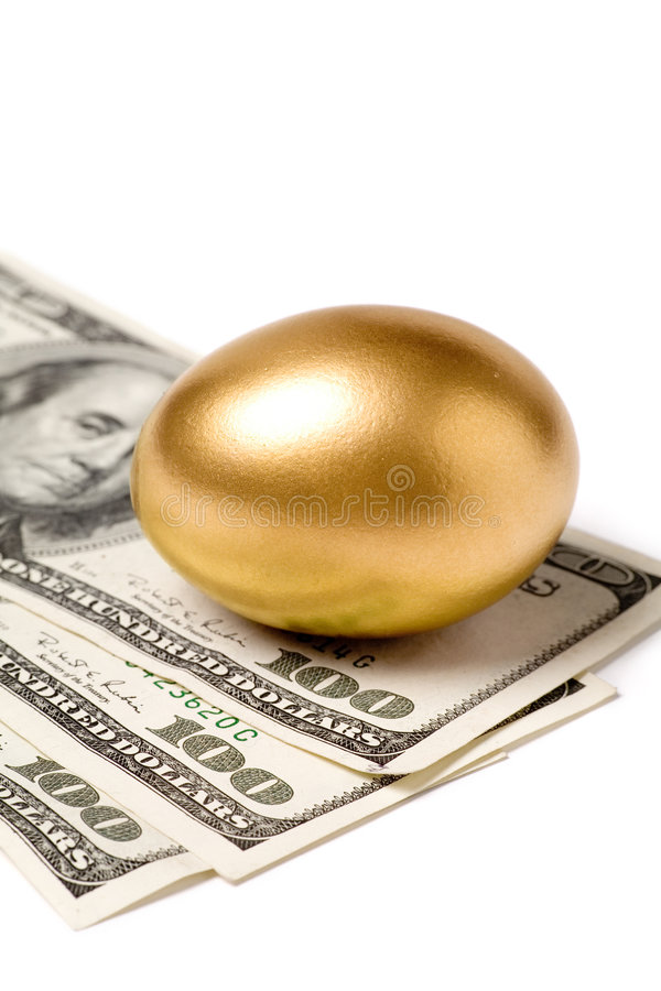 Huevo y dólares de oro imagen de archivo