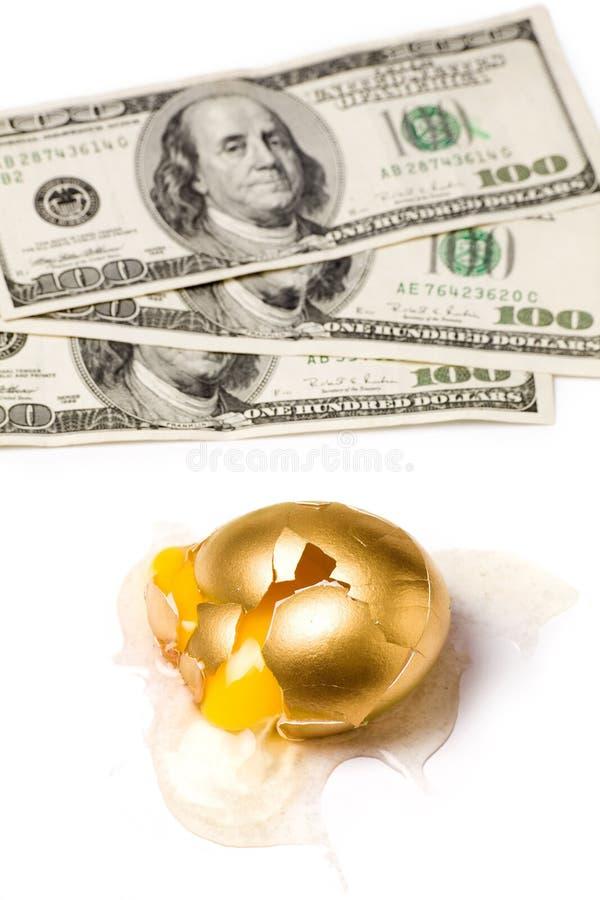 Huevo y dólares de oro quebrados imagen de archivo libre de regalías