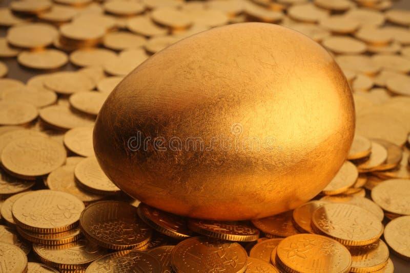 Huevo y monedas del oro imagenes de archivo