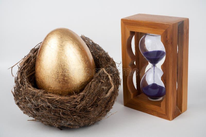 Huevo y reloj de arena de oro fotografía de archivo libre de regalías