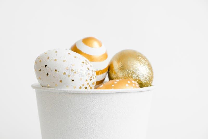 Huevos adornados de oro de Pascua en cubo en el fondo blanco Concepto mínimo de pascua Tarjeta de pascua feliz con el espacio de  fotografía de archivo