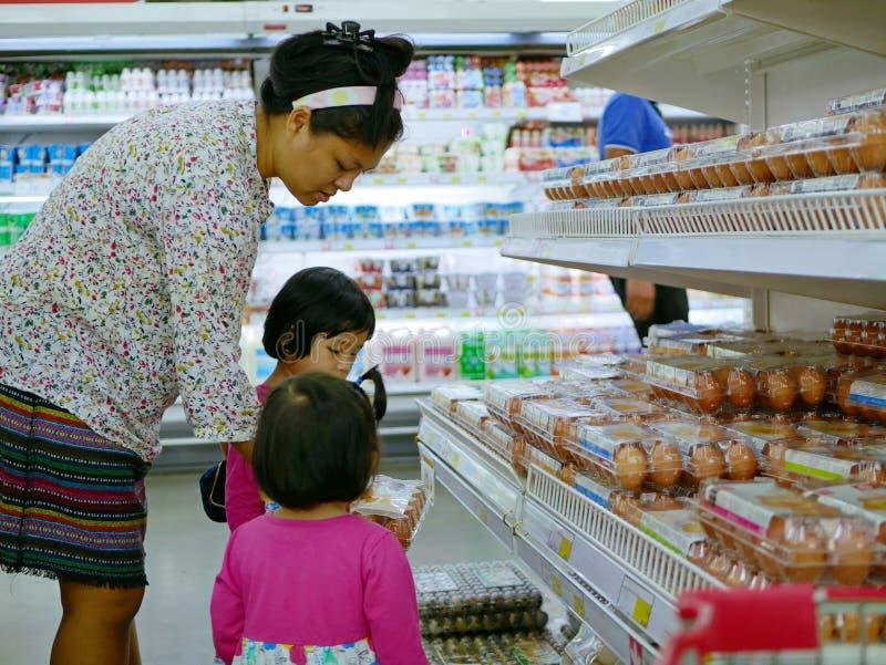 Huevos asiáticos del pollo de la demostración de la madre que ella quiere comprar a sus dos pequeñas hijas en un supermercado fotografía de archivo libre de regalías