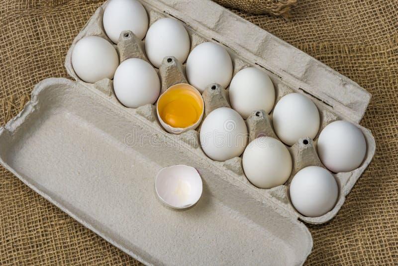 Huevos blancos con huevo roto imágenes de archivo libres de regalías