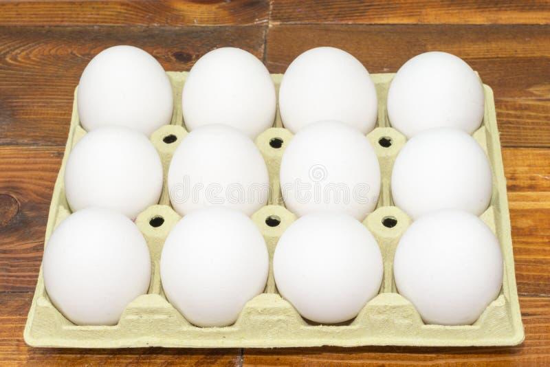 Huevos blancos del pollo en una caja de cartón imagen de archivo libre de regalías