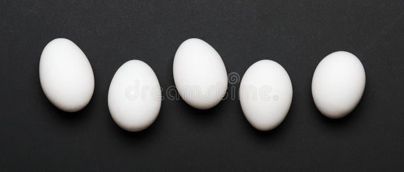 Huevos blancos en un fondo negro bandera Alimento sano Visión superior, endecha plana fotografía de archivo