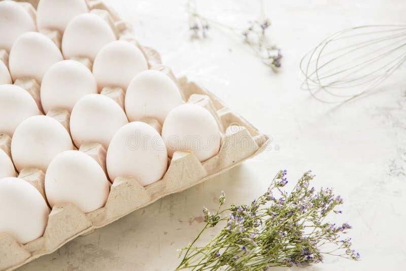 Huevos blancos en una caja en un fondo ligero fotos de archivo libres de regalías