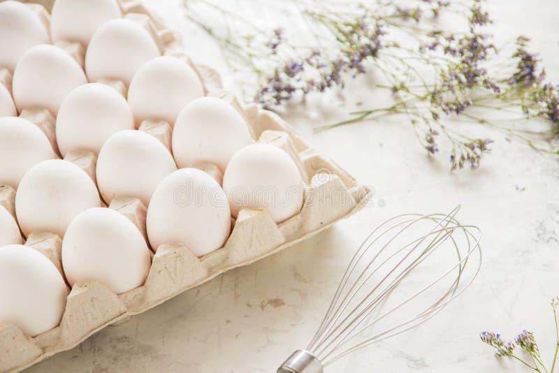 Huevos blancos en una caja en un fondo ligero imagenes de archivo