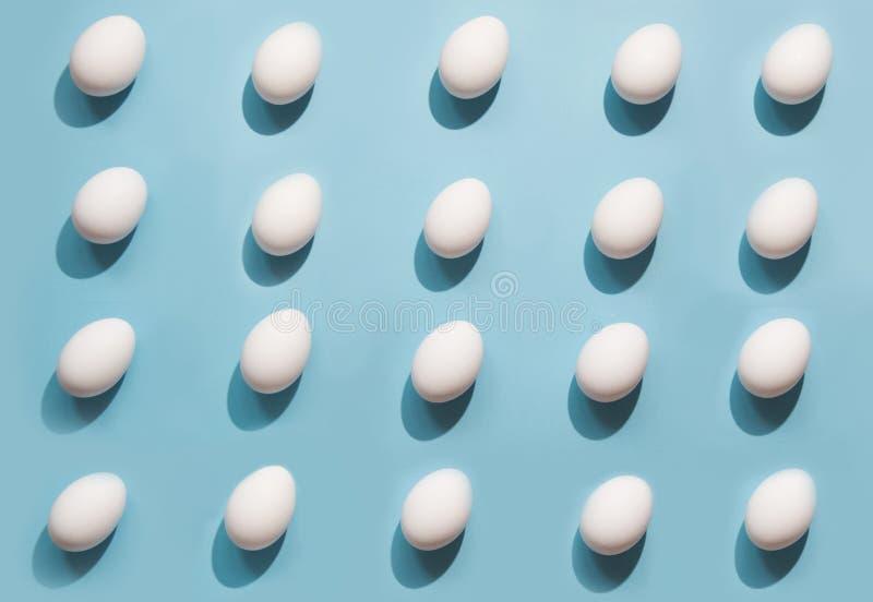 Huevos blancos orgánicos en azul Modelo abstracto Huevos en isométrico fotos de archivo libres de regalías