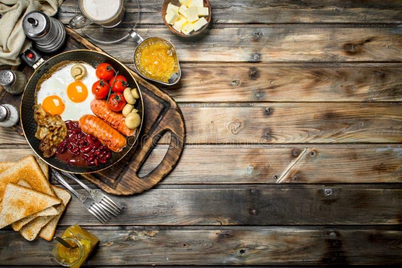 Huevos breakfastFried ingleses con las salchichas, el pan frito y el café aromático imagen de archivo libre de regalías