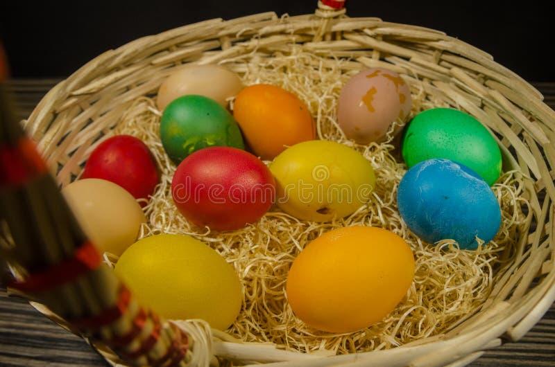 Huevos coloreados en cesta de mimbre imagenes de archivo