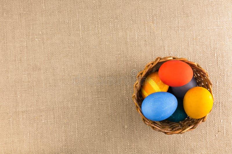 Huevos coloreados en la cesta, preparada para el día de fiesta de Pascua foto de archivo