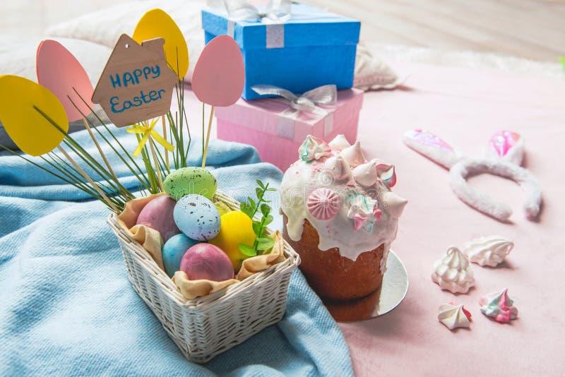 Huevos coloreados que localizan cerca de la torta deliciosa de pascua foto de archivo libre de regalías