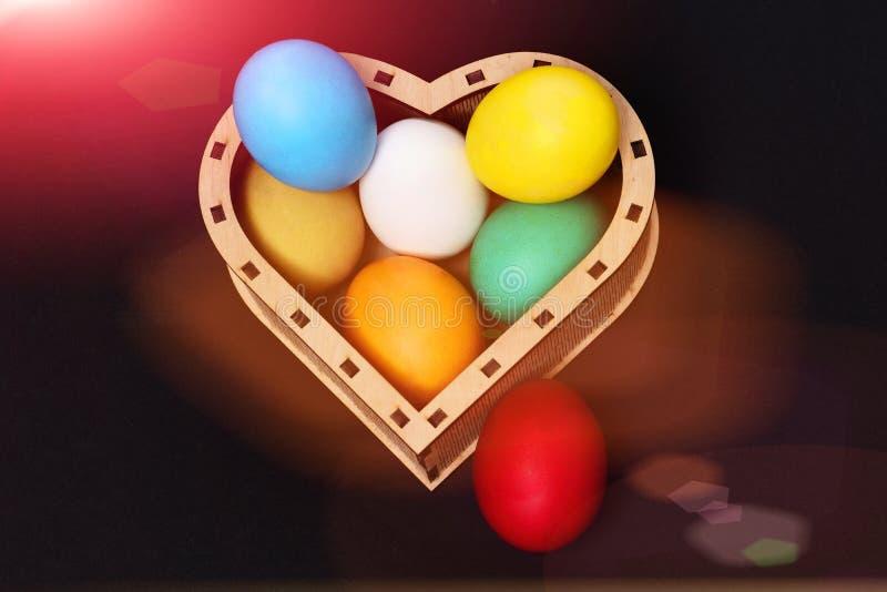 Huevos coloridos de Pascua en la caja de madera del corazón aislada en negro imagen de archivo