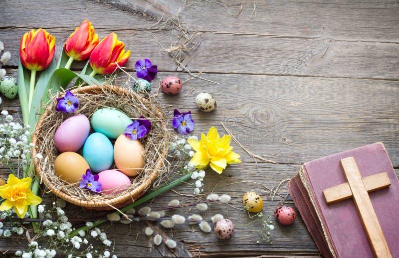 Huevos coloridos de Pascua en la jerarquía con las flores en los tableros de madera del vintage con la biblia y la cruz imagen de archivo libre de regalías