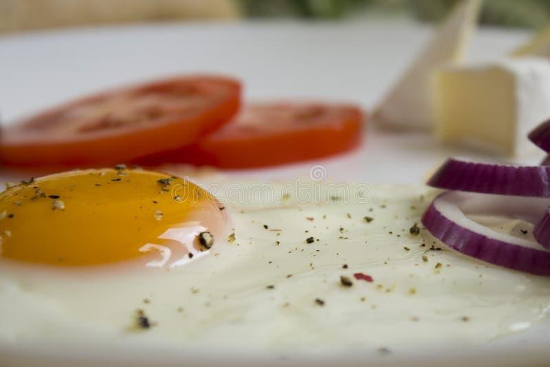 Huevos con un tomate y una cebolla roja imagen de archivo libre de regalías