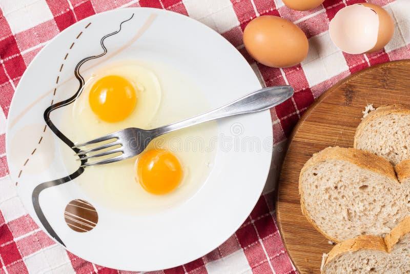 Huevos crudos en la placa con la bifurcación Preparación de los huevos para un desayuno imágenes de archivo libres de regalías