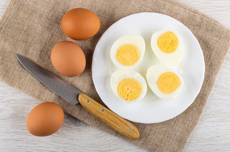 Huevos, cuchillo de cocina en la arpillera, mitades de huevos hervidos pelados en placa en la tabla Visi?n superior fotos de archivo