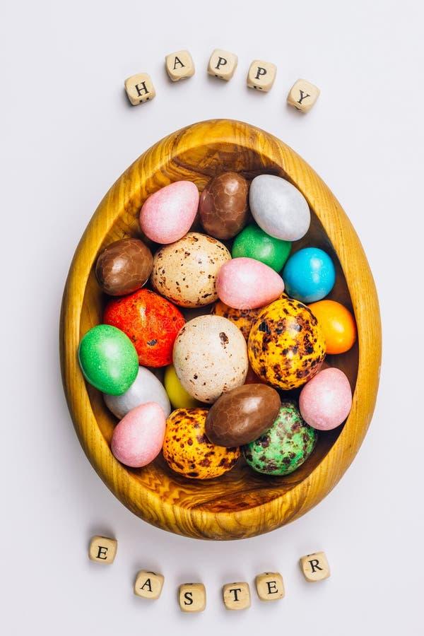 Huevos de caramelo azucarados dulces de Pascua en un cuenco de madera imagen de archivo