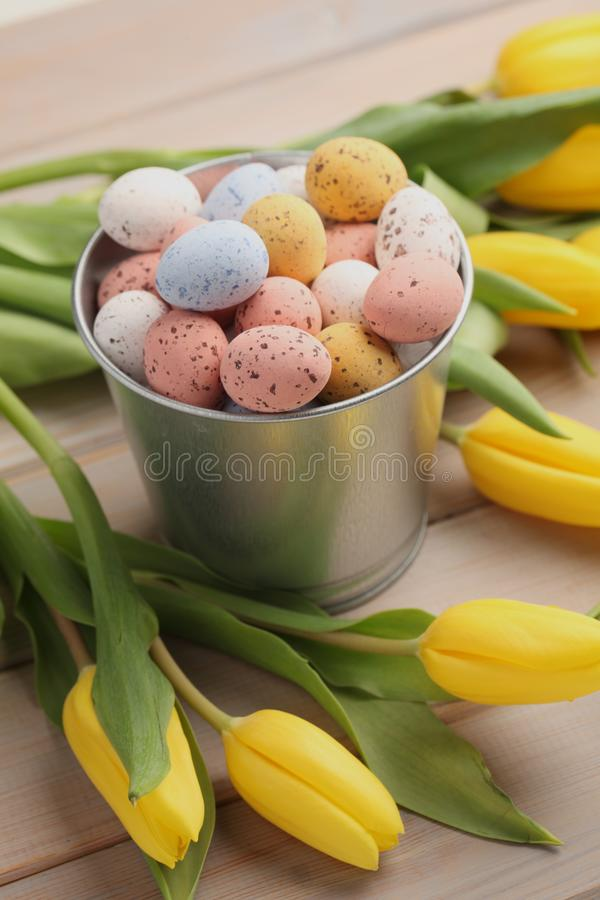 Huevos de caramelo coloridos de pascua con los tulipanes amarillos fotografía de archivo
