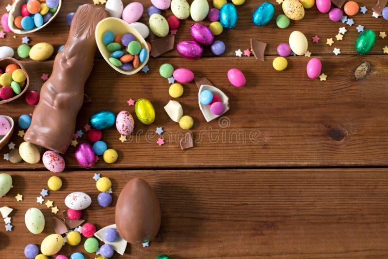 Huevos de chocolate, conejito de pascua y caramelos en la madera imagen de archivo