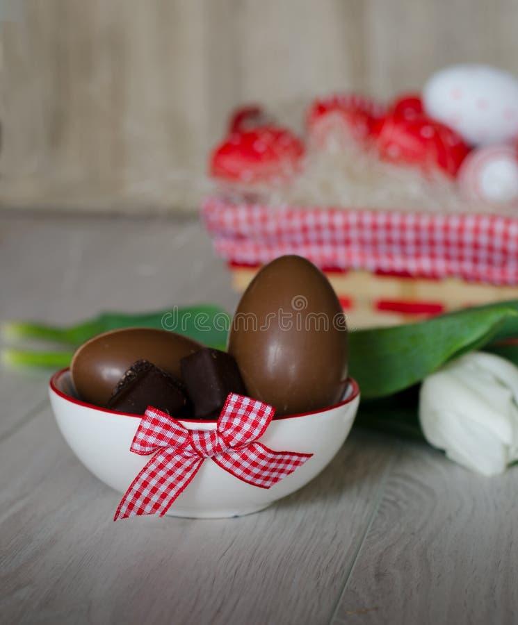 Huevos de chocolate en cuenco en la tabla de madera Huevos de Pascua en cesta imagenes de archivo