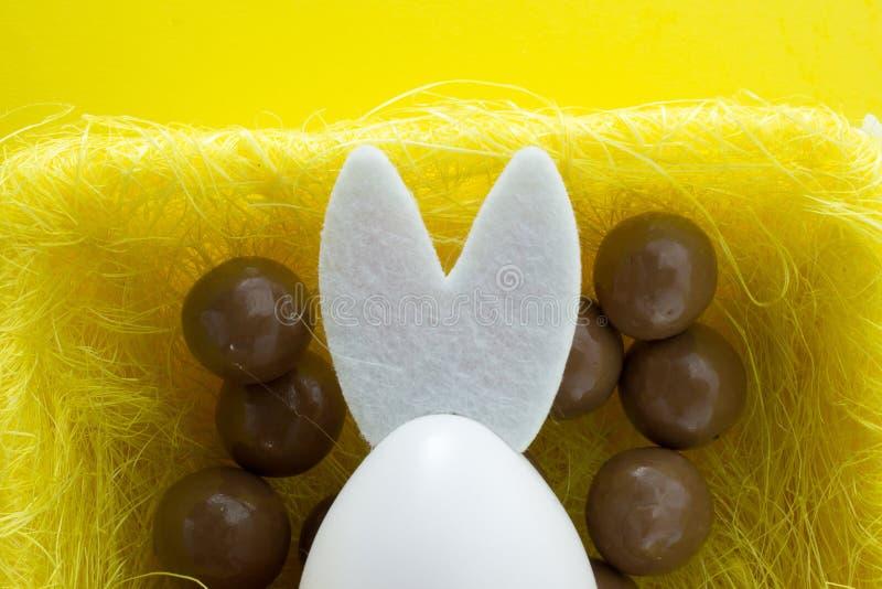 Huevos de chocolate en la jerarquía y el conejito de pascua, decoraciones del día de fiesta de Pascua, fondo del pájaro del conce imágenes de archivo libres de regalías