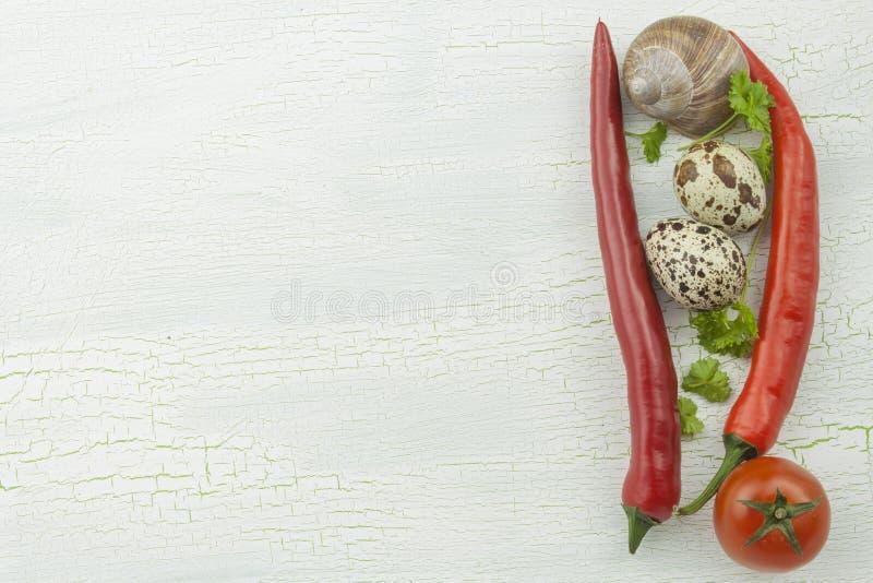 Huevos de codornices, cáscaras del caracol y verduras en un viejo del disco sombreado imagenes de archivo
