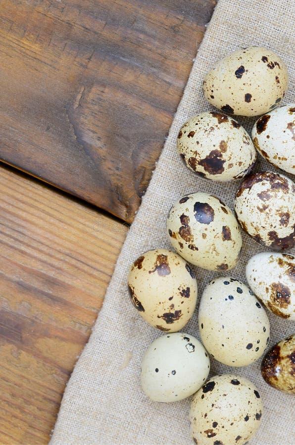 Huevos de codornices en el despido en una superficie de madera del marrón oscuro, visión superior, imagen de archivo