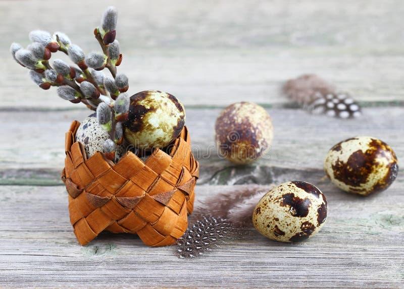 Huevos de codornices en una cesta en un fondo de madera, Pascua fotografía de archivo libre de regalías
