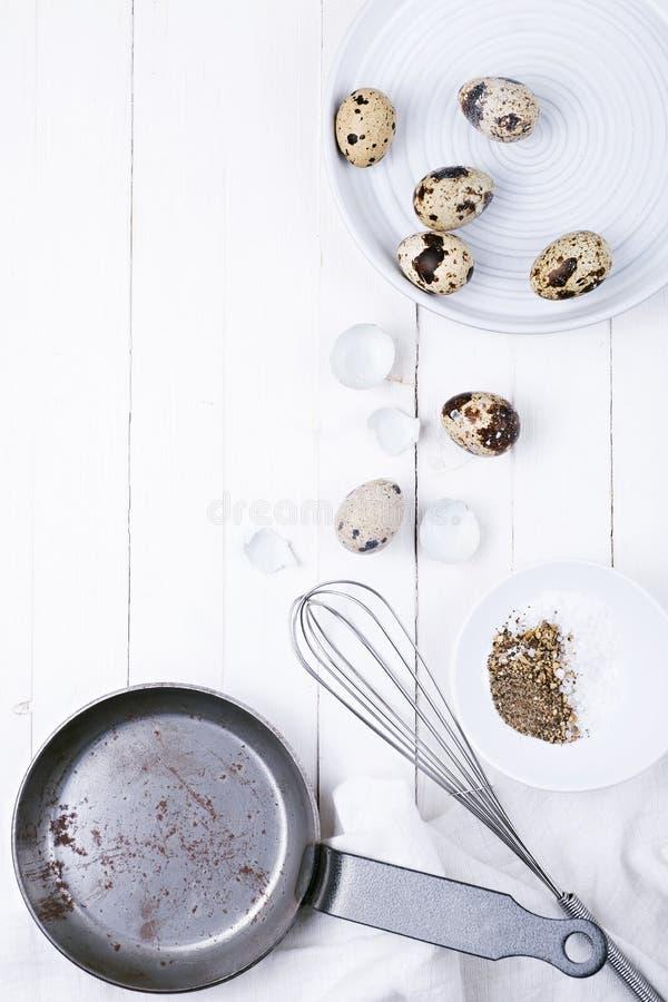 Huevos de codornices en una placa, una cáscara, un batidor para batir y un sartén en un fondo de madera blanco Visi?n desde arrib imágenes de archivo libres de regalías