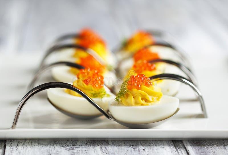Huevos de Deviled con el caviar rojo en una cuchara imagen de archivo libre de regalías