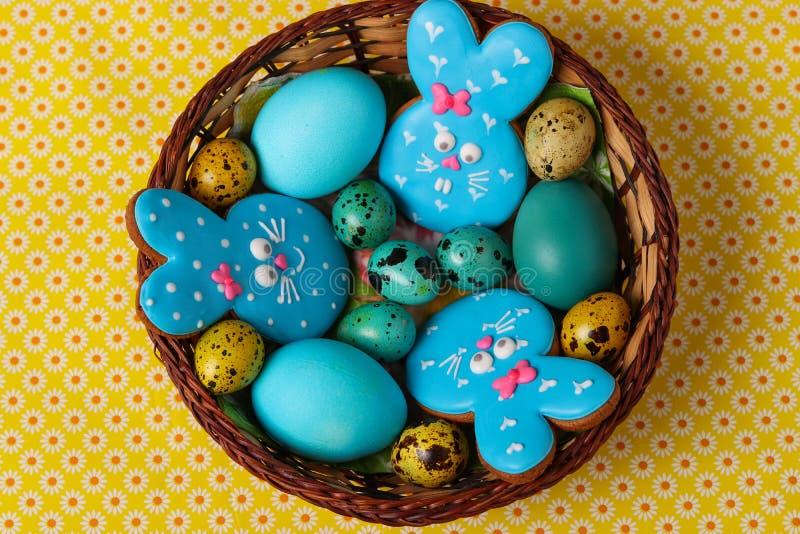 Huevos de los conejos de los panes de jengibre de Pascua, amarillos y azules del pollo y de codornices en una cesta de mimbre, vi imagen de archivo
