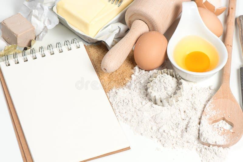 Huevos de los ingredientes del libro y de la hornada de la receta, harina, azúcar, mantequilla, y fotos de archivo libres de regalías