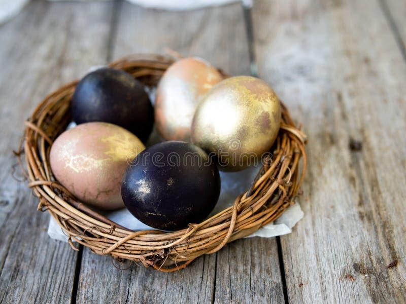 Huevos de oro y negros en una jerarquía en un viejo fondo de madera Copie el espacio, foco selectivo, cierre para arriba Huevos p imagenes de archivo