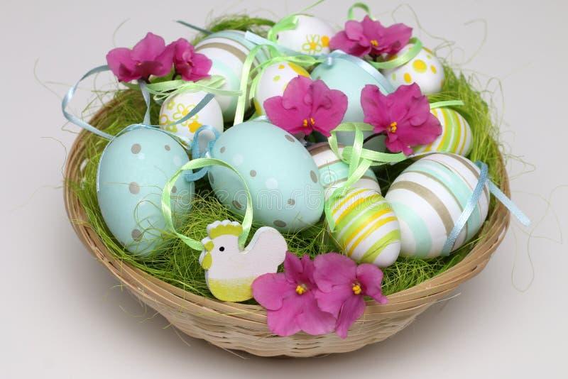 Huevos de Pascua adornados con las flores rosadas en una cesta baja fotografía de archivo