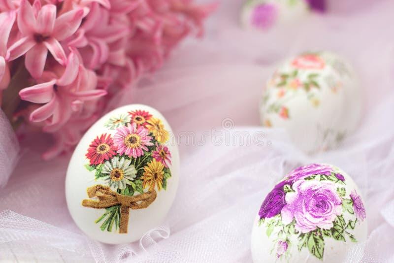 Huevos de Pascua adornados con las servilletas de papel y las flores en el fondo blanco de Tulle; técnica del decoupage imágenes de archivo libres de regalías
