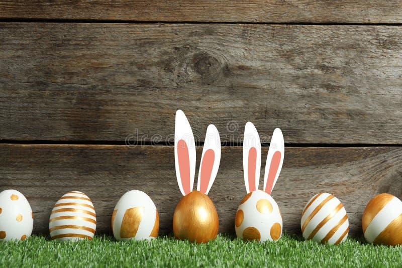 Huevos de Pascua adornados y los oídos del conejito lindo en hierba verde contra fondo de madera imagen de archivo
