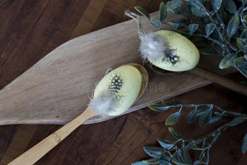 Huevos de Pascua amarillos con las plumas en cuchara de madera fotografía de archivo libre de regalías