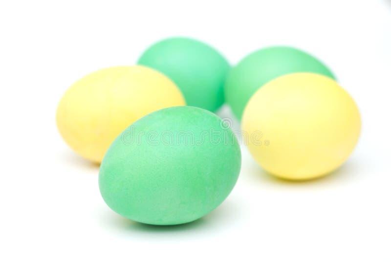 Huevos de Pascua amarillos y verdes aislados en blanco foto de archivo libre de regalías