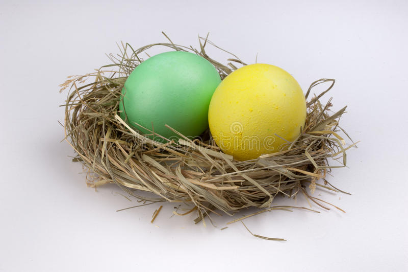 Huevos de Pascua amarillos y verdes en la jerarquía aislada en blanco fotografía de archivo libre de regalías
