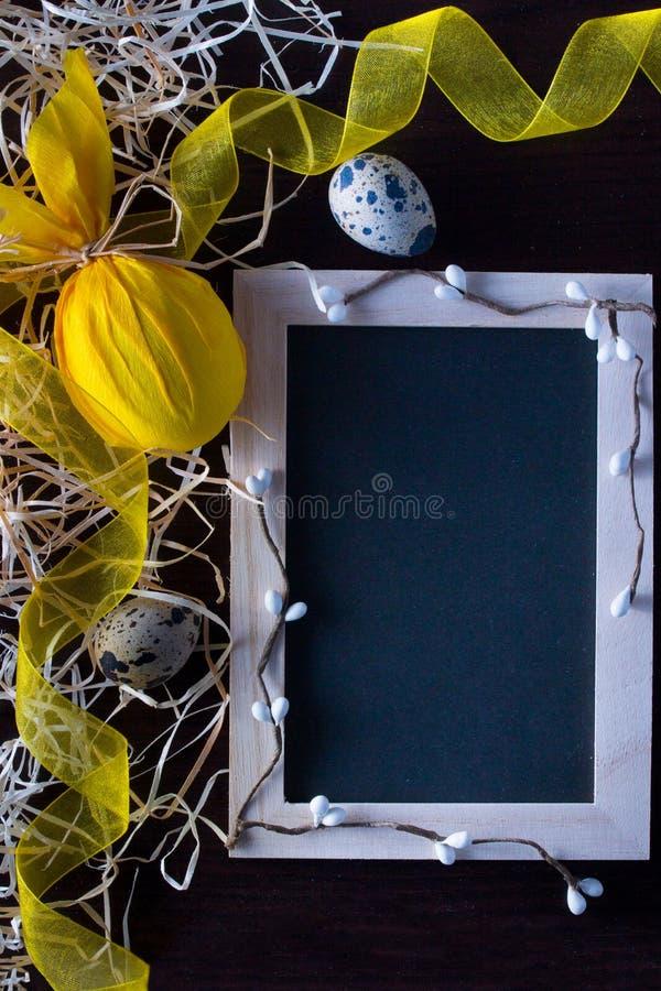 Huevos de Pascua bajo la forma de conejo con la pizarra para escribir el texto, la rama del sauce, la cinta amarilla y los huevos imágenes de archivo libres de regalías