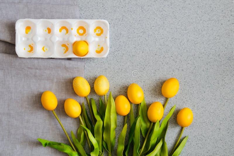 Huevos de Pascua bajo la forma de ramo de tulipanes en la sobremesa hecha de piedra de acrílico artificial El concepto creativo d fotografía de archivo libre de regalías