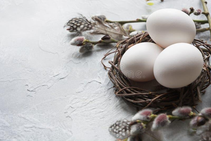 Huevos de Pascua blancos en sauce de la jerarquía y de la primavera en la tabla del vintage imagen de archivo