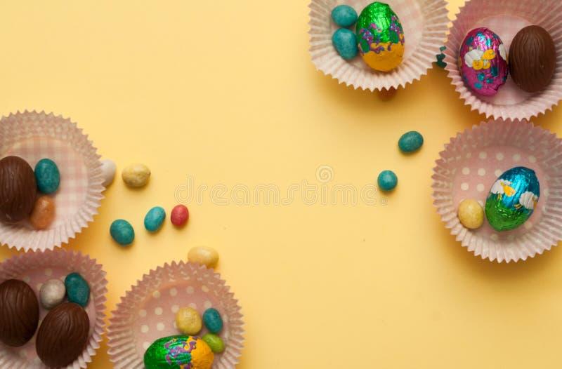 Huevos de Pascua brillantes coloridos en fondo azul Fondo de Pascua imagenes de archivo
